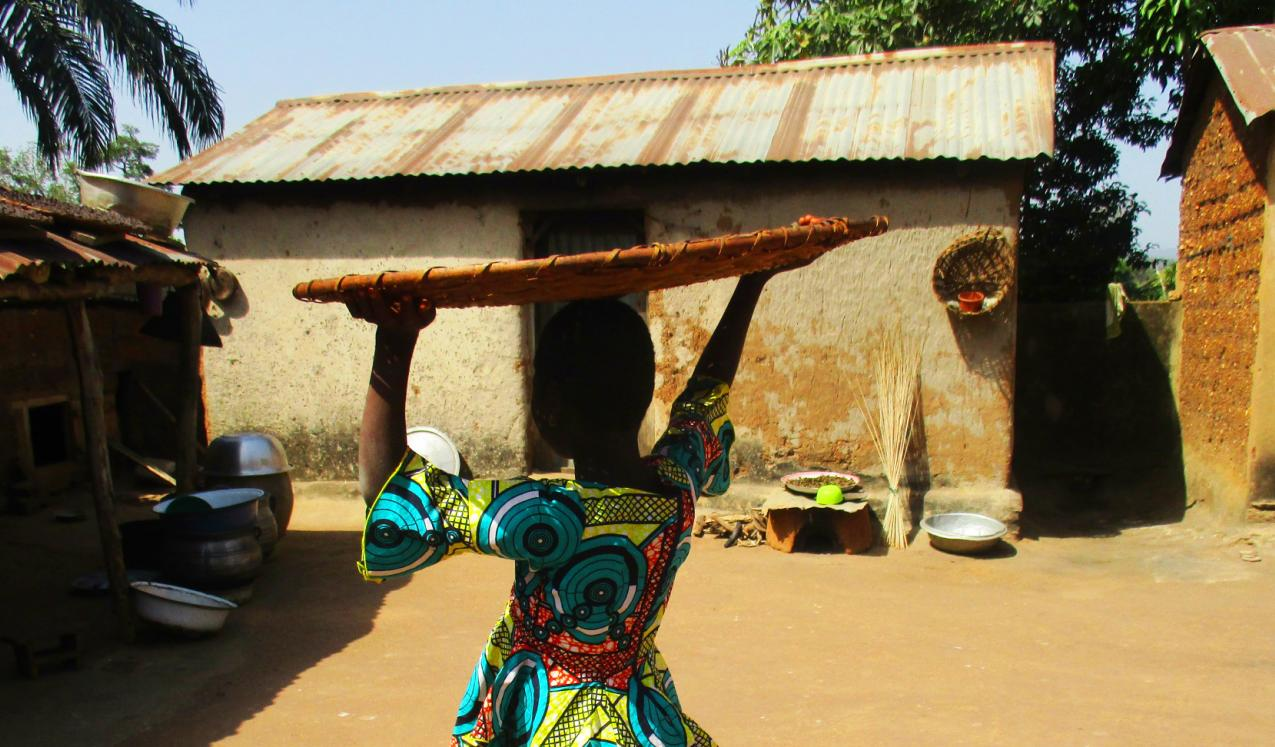 A lady carrying a large flat basket on her head. Credit: Plan International Togo