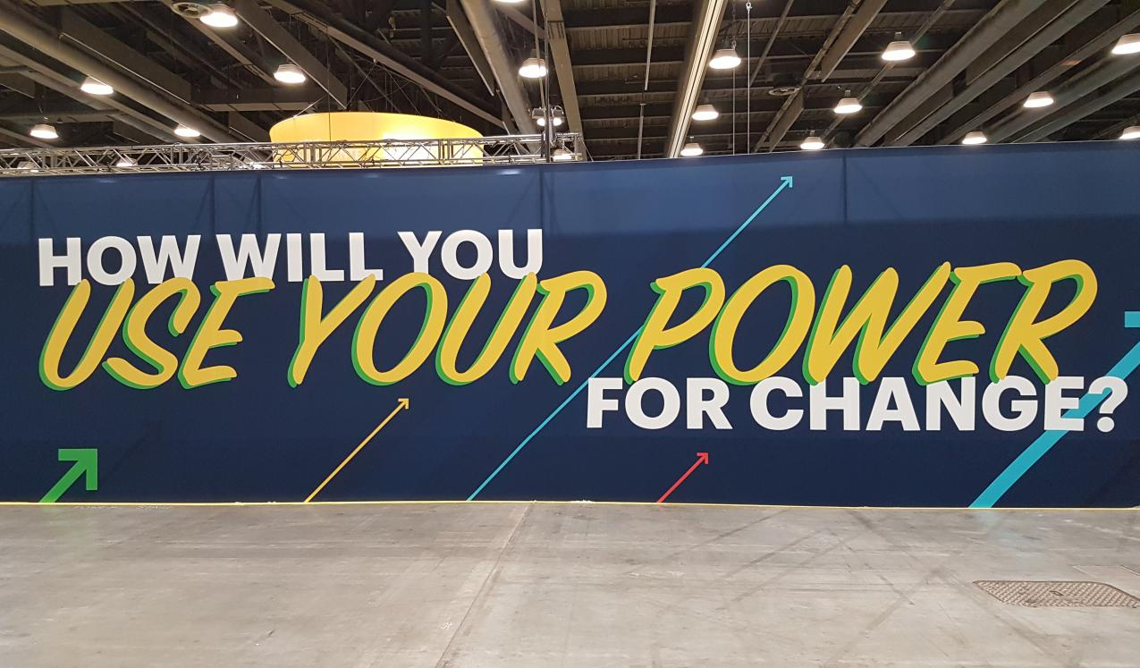 "A banner at the conference asking ""how will you use your power?"""