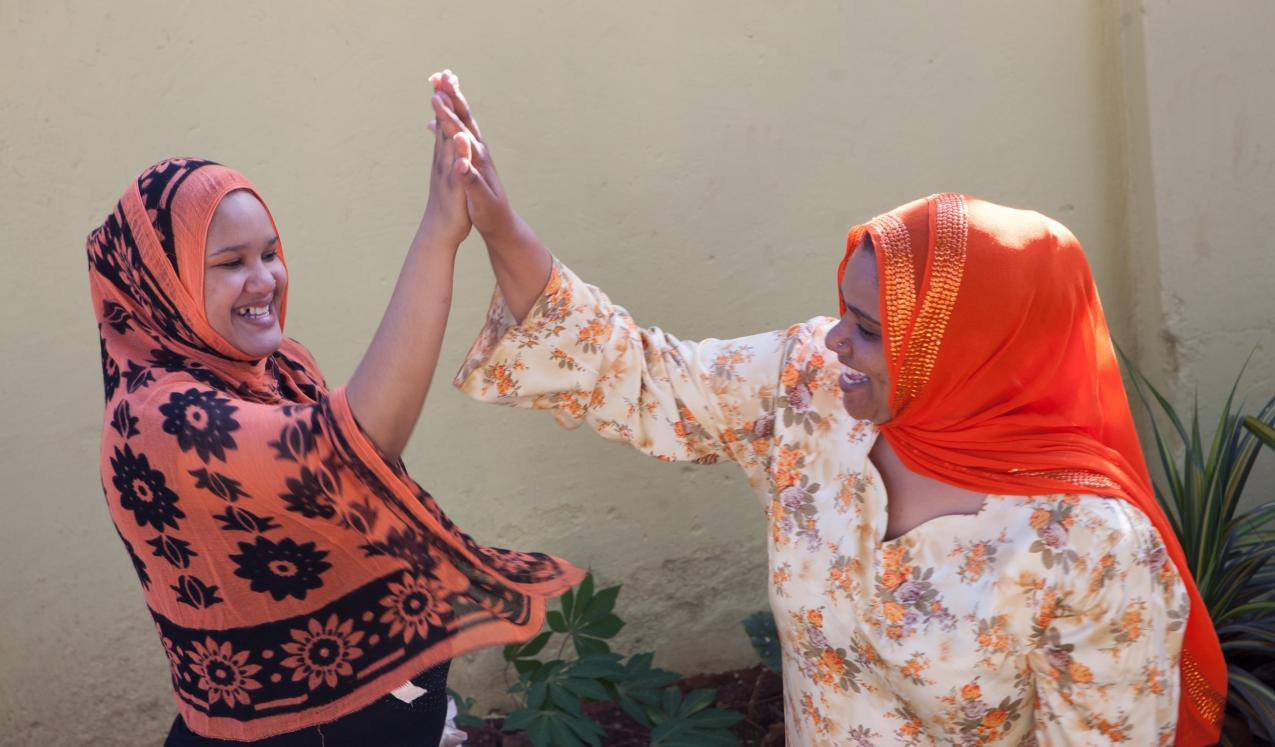 Two women 'high five-ing' © Raising Voices