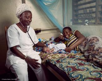 A nurse at a health center in Athiémé,  Benin, examines a newborn beside the  proud mother. © Stephan Gladieu / World Bank