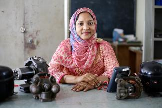 Shirina Akter with refrigeration machinery she teaches with in her classroom at UCEP school, Dhaka, Bangladesh ©UKAID