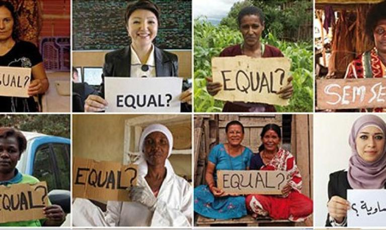 Women holding placards with the word EQUAL on them