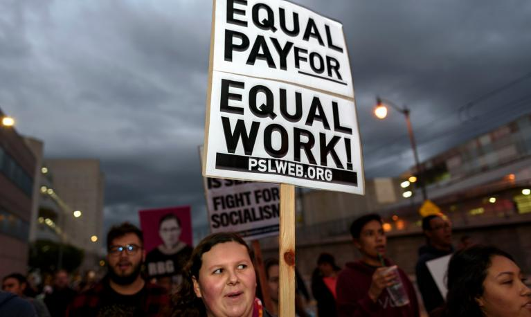 "A woman holds a placard at a rally reading "" Equal pay for equal work."" Copyright Ronen Tivony/LightRocket/Getty Images"""