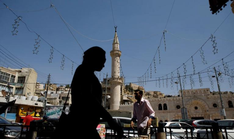 A women in silhouette walks through a square in Jordan. © Annie Sakkab/Bloomberg/Getty Images