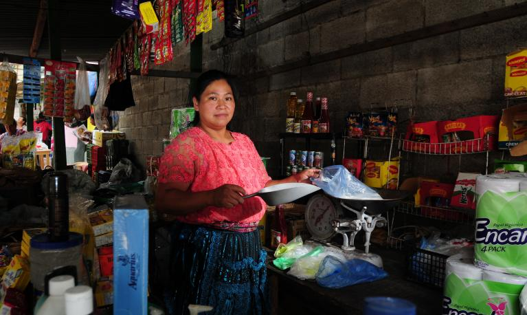 A woman attends her stall at a market in Guatemala City. © Maria Fleischmann / World Bank