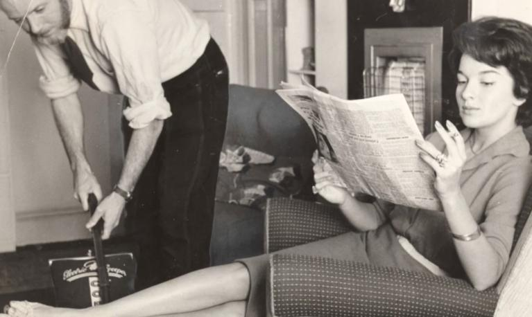 An old black and white photo of a man vacuuming the floor whilst a women reads the paper. © BERNSEN'S INTERNATIONAL PRESS SERIES