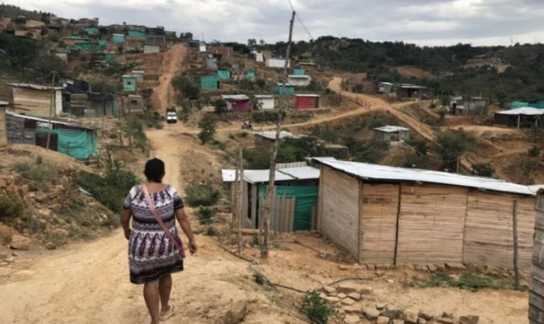 A woman walks on the outskirts of a makeshift suburb of a Colombian city, which is inhabited largely by returned Colombians and Venezuelans.