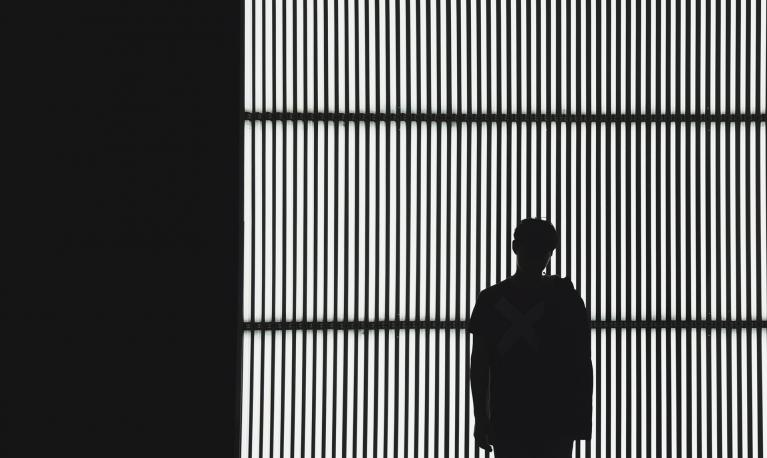 Silhouette of a man against a slatted backdrop. © Nicholas Kwok/Unsplash