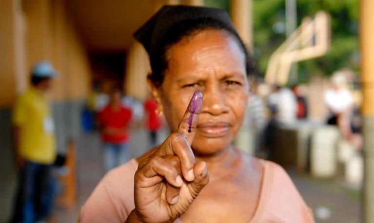 A woman holds up her stained finger after voting today in Timor-Leste's presidential run-off poll . © UN Photo/Bernardino