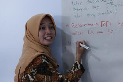 A participant writes notes on a white board at the convening