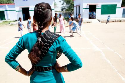 The back of a school girl in India looking at her friends in the playground. Credit: Charlotte Anderson