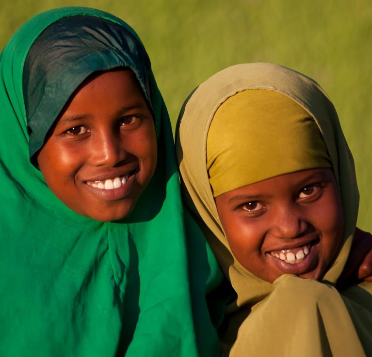 Two girls with headscarves on smile for the camera.