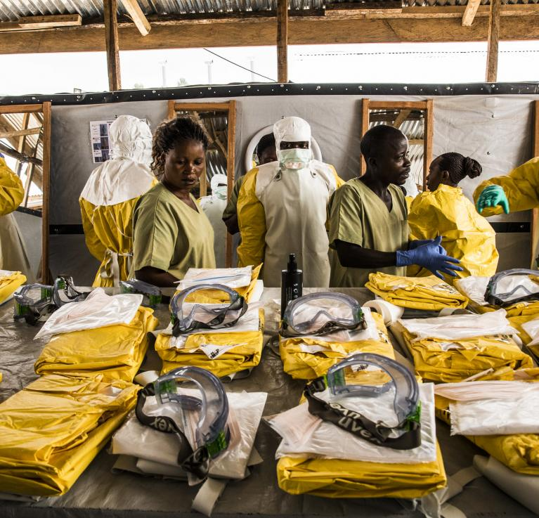 Health workers put on their personal protective equipment before treating people suspected of having Ebola at the Ebola Transition Center in the Democratic Republic of Congo. © World Bank/Vincent Tremeau