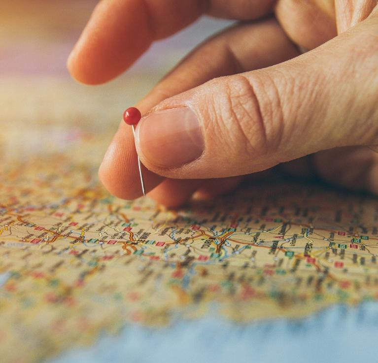 A hand putting a pin in a map.