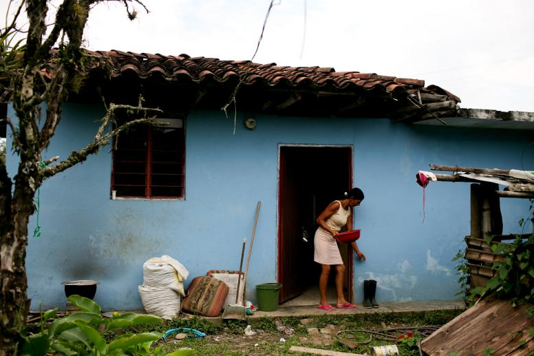 A woman outside her sky blue home near Santander, Colombia. © Charlotte Kesl / World Bank